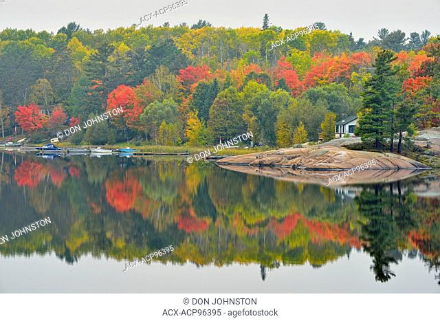 Autumn reflections in the Key River, with holiday camps and watercraft, Key River, Ontario, Canada