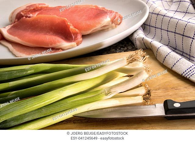 organic spring onion and raw bacon on a wooden board to prepare irish colcannon