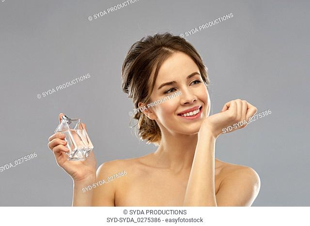 happy woman with perfume over gray background
