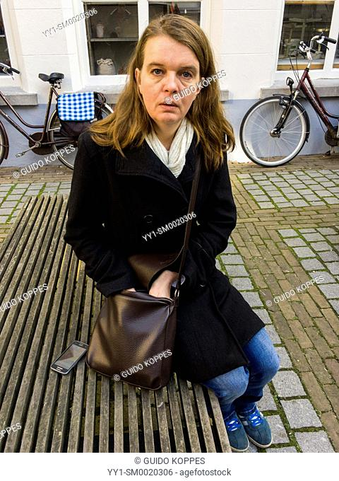 Breda, Netherlands. Mid adult caucasian woman grabbing for items inside her ladies purse while sitting on a wooden bench outside a museum