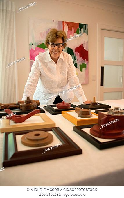 A middle aged woman shows off her artistic project of mounted wooden objects