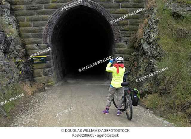 Woman cyclist takes a photo at a tunnel on the Central Otago Rail Trail, South Island, New Zealand