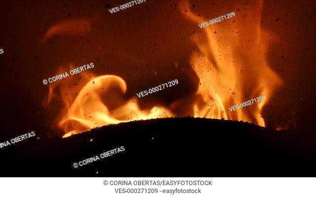 Closeup of flame burning inside stove and visible residue of burnt pellets deposited on the stove window