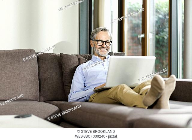 Smiling man sitting on couch in his living room using laptop