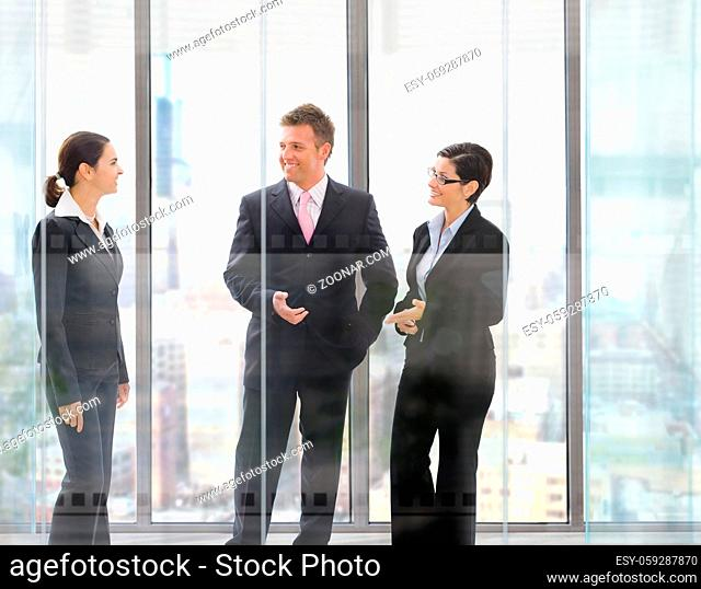 Three happy businesspeople standing in front of office windows, talking and smiling
