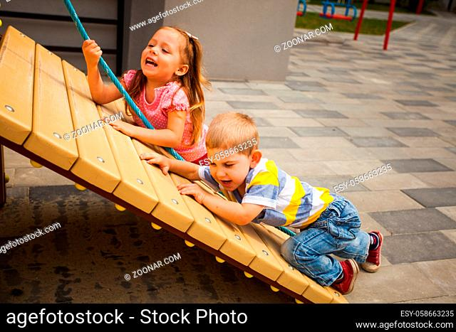 Children trying climbing the rope on playground outdoors