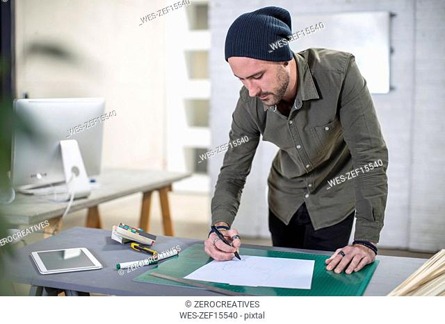 Young man taking notes at desk in office