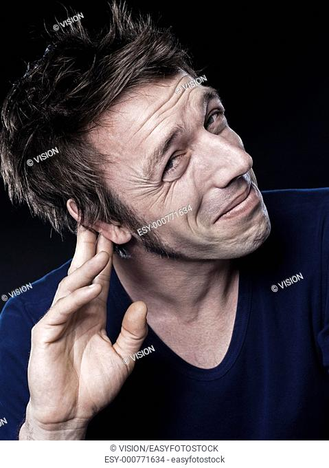 studio portrait on black background of a funny expressive caucasian man with hearing problem