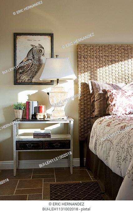 Lamp on bedside table in domestic bedroom
