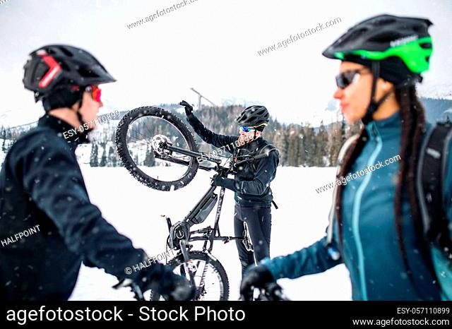A group of young mountain bikers standing on road outdoors in winter