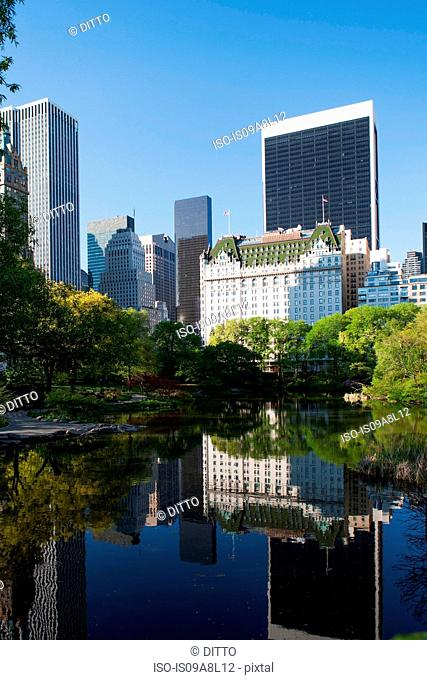 Buildings on lake in Central Park, New York City, USA