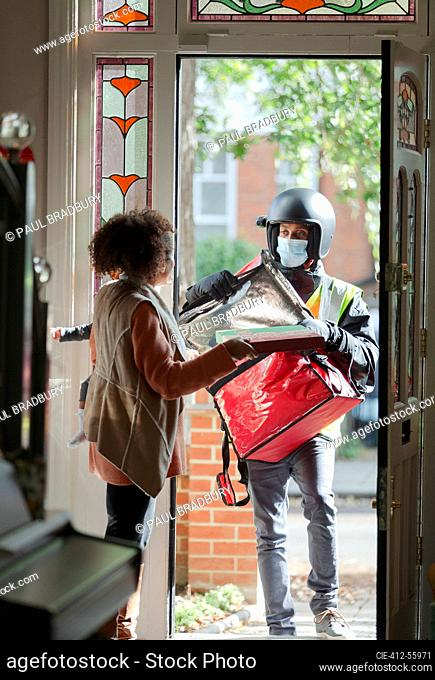 Woman receiving pizza from delivery man in face mask at front door