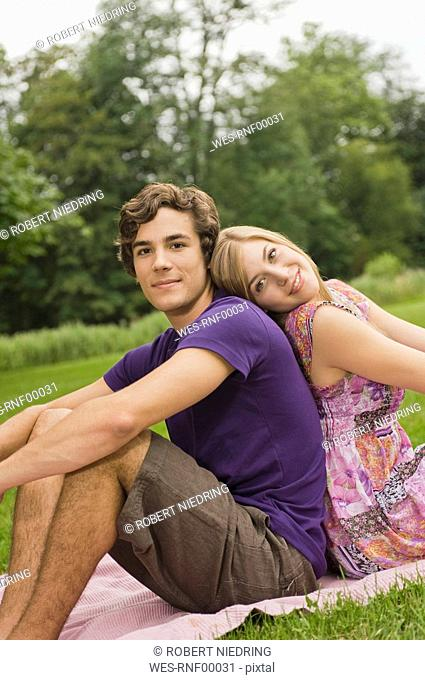 Germany, Bavaria, Starnberger See, Young couple sitting on meadow back to back