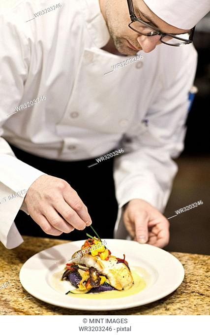 A Caucasian male chef putting the finishing touches on a plate of fish in a commercial kitchen