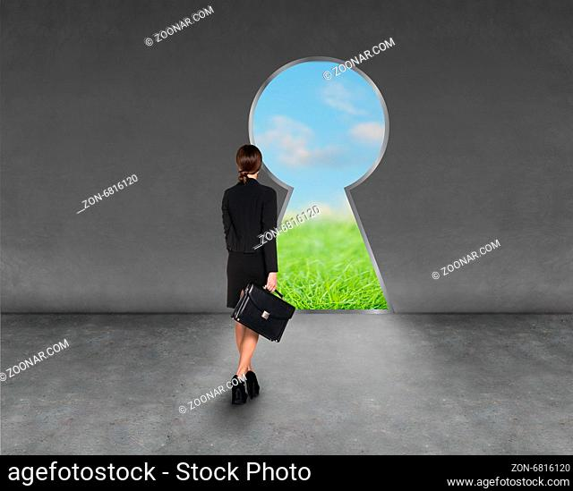 Composite image of businesswoman standing back to camera in room with keyhole shaped door