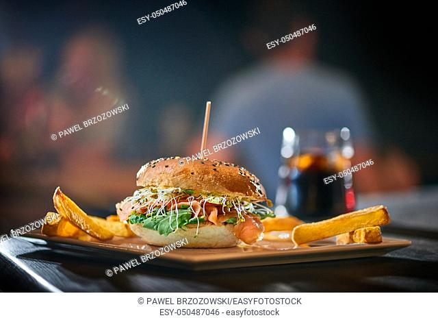 Salmon burger with wooden spike served with french fries. Blurred pub background. Copy space