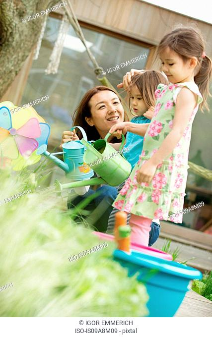 Mother and two daughters with toy watering cans in garden