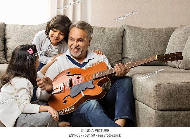 Grandfather playing guitar for grandchildren at home