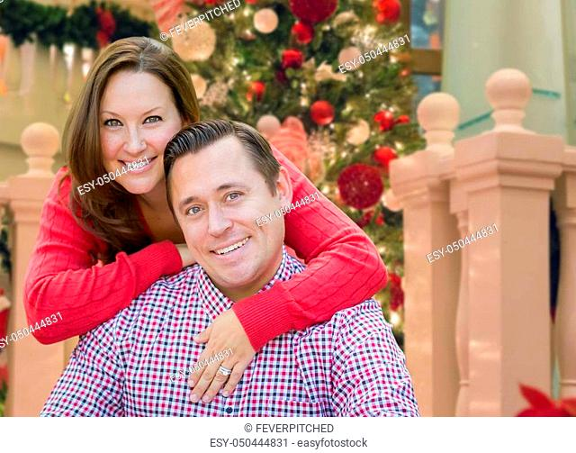 Caucasian Couple Hugging In Front of Decorated Christmas Tree