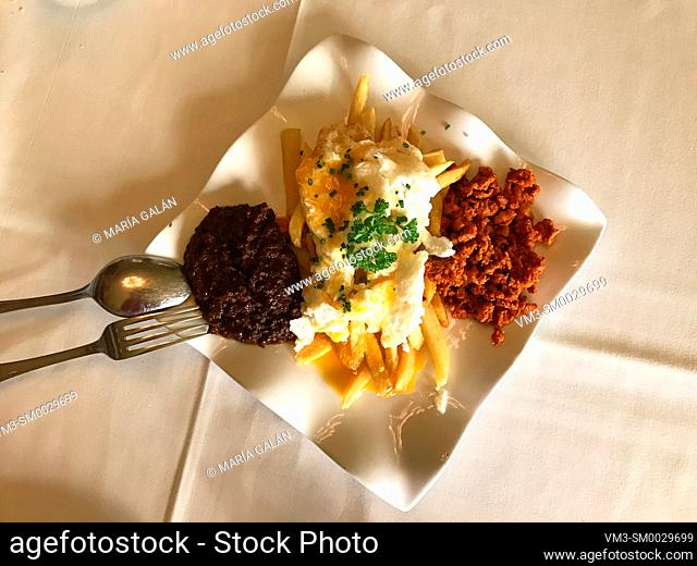 Fried eggs with picadillo, chips and morcilla. View from above