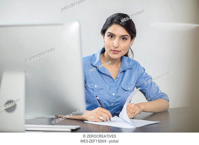 Portrait of businesswoman taking notes at desk in office