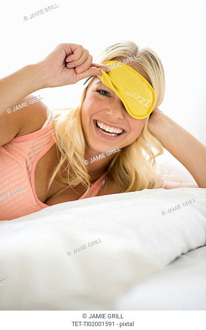 Portrait of smiling woman with eye mask on