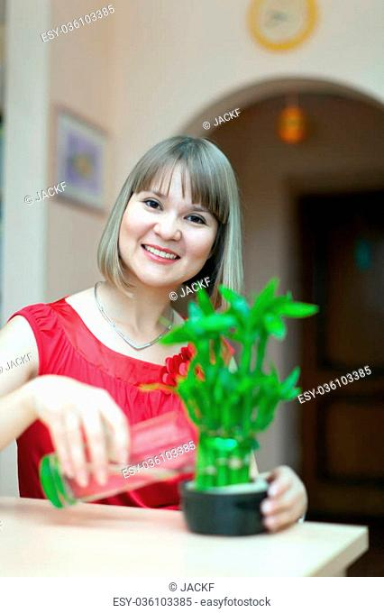 Girl with lucky bamboo plant at her home