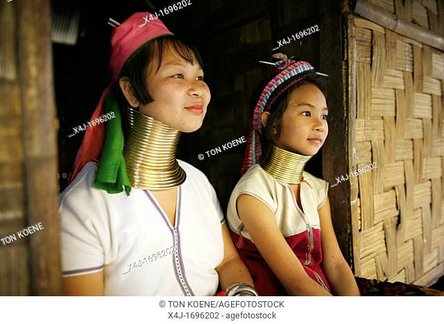 Profiles of two Longneck girls sitting in front of a house Approximately 300 Burmese refugees in Thailand are members of the indigenous group known as the...