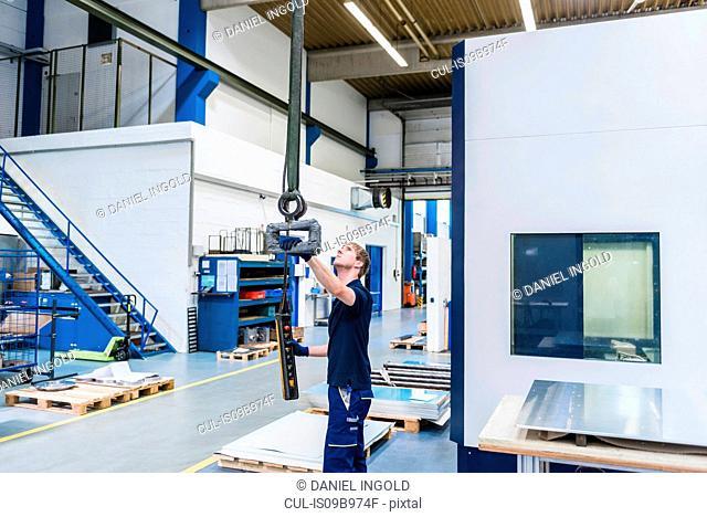 Factory worker using industrial equipment in factory