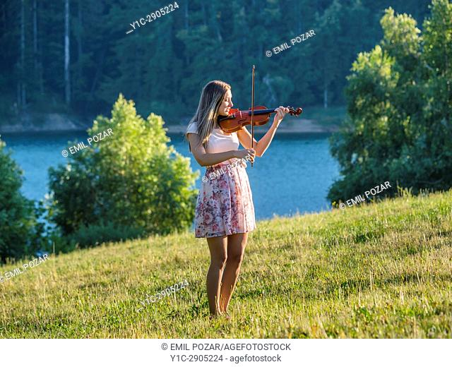 Young female musician violinist in nature near lake playing violin instrument. Croatia