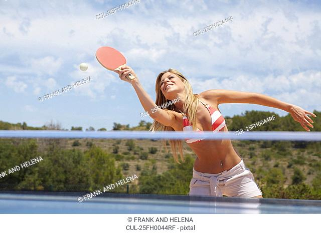 Woman in a game of table tennis outdoors