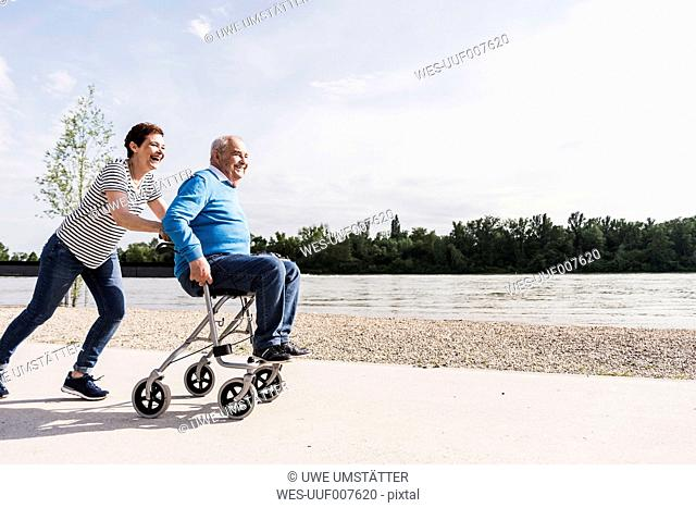Woman pushing her old father sitting on wheeled walker