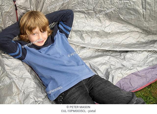 Boy resting on tent