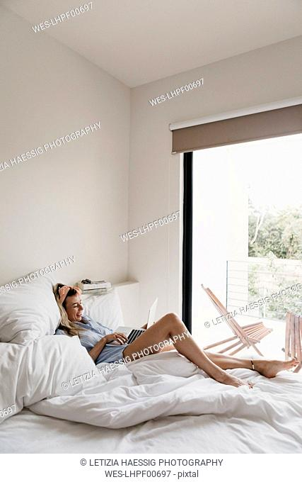 Smiling young woman using laptop in bed