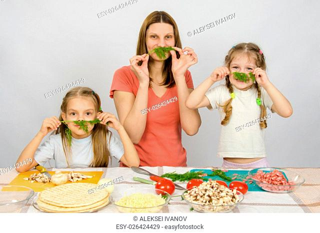 Young housewife with two daughters having fun holding sprig of parsley as a mustache at the kitchen table when sharing cooking
