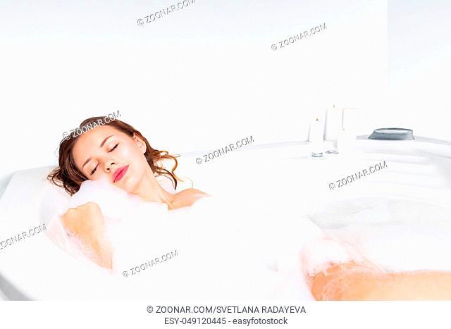 Young beautiful woman enjoying bathing in bathtub
