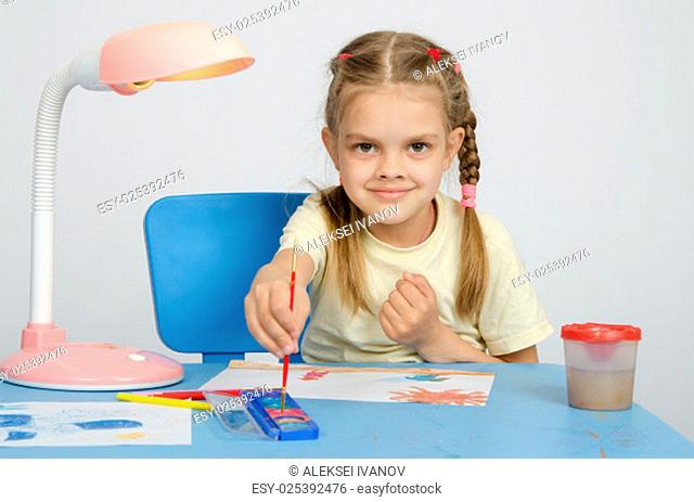 Six year old girl Europeans draws paints on a sheet of sitting at the table