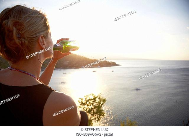 Woman drinking bottle of beer looking out to sea, Amed, Jemeluk beach, Bali, Indonesia