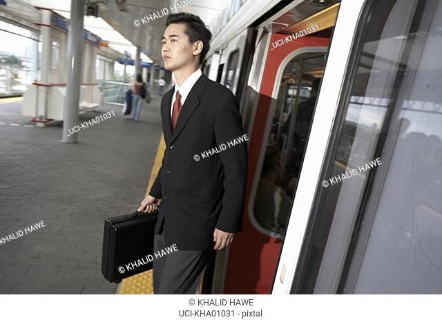 Asian businessman departing train