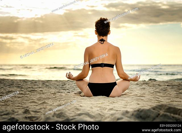 beautiful woman in a black swimsuit meditating on the beach at sunset