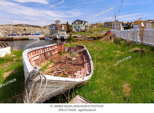 A old dilapidated fishing vessel with homes in the background. Brigus, Newfoundland, Canada