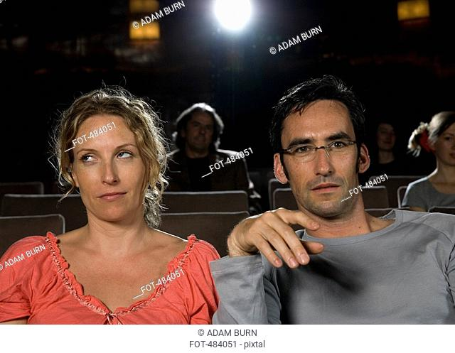 A woman rolling her eyes whilst sitting next to a man in a movie theater