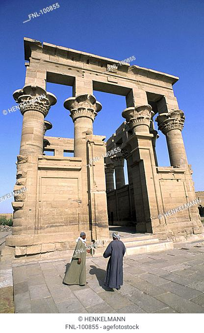 Two people near old egyptian ruins, Temple of Philae, Aswan, Egypt