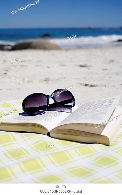 Sunglasses on book on beach