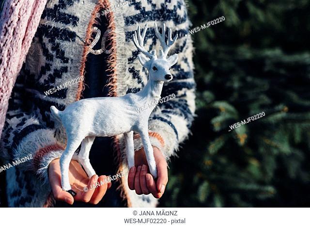 Little girl holding toy reindeer