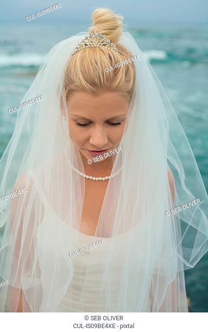 Bride with head bowed by sea