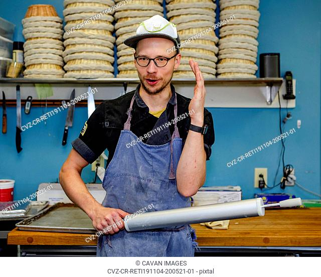 A professional baker talks with rolling pin in hand in kitchen