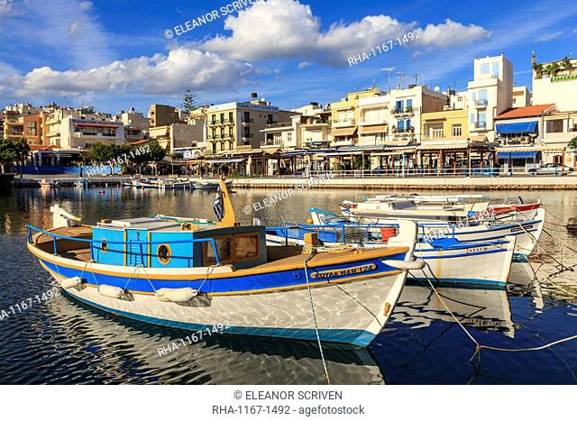 Small fishing boats reflected in Voulismeni Lake, Agios Nikolaos, Lasithi, Crete, Greek Islands, Greece, Europe