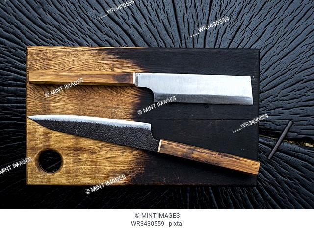 High angle close up of two handmade knives on wooden cutting board