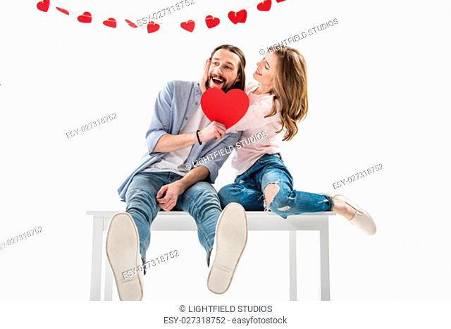 Young happy couple in love holding red paper heart and sitting on table on white